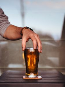 man picking up a glass of beer